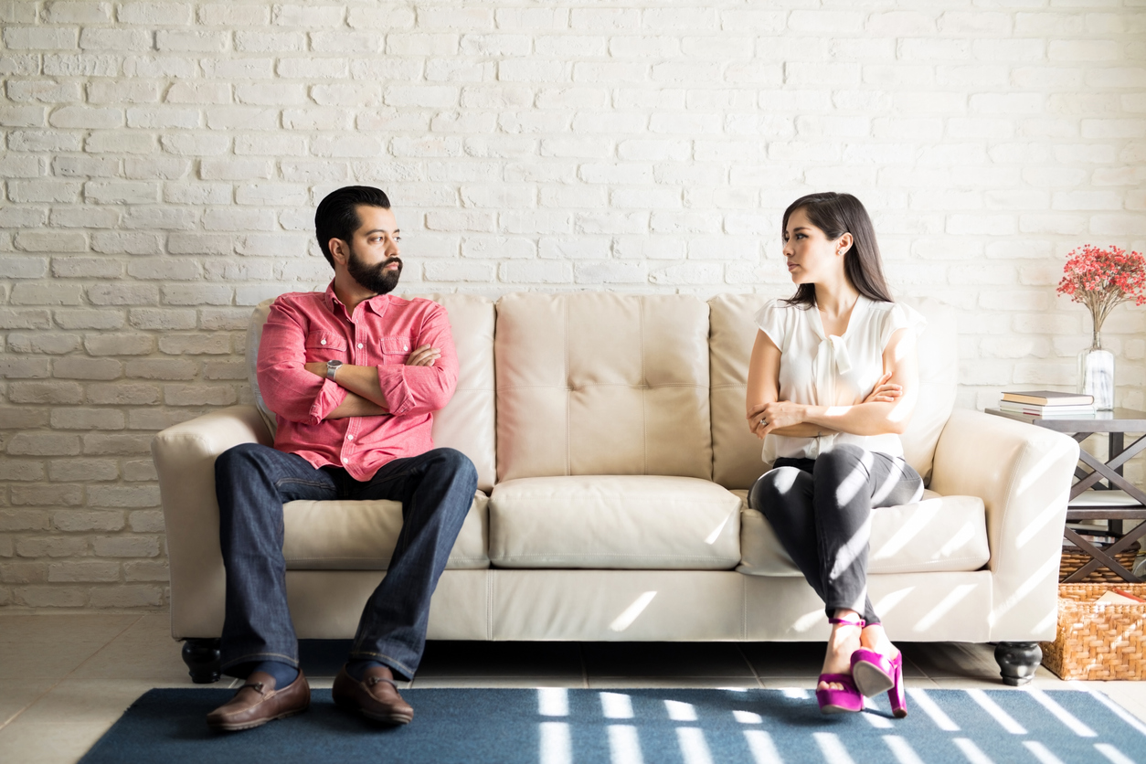 Husband and wife sitting on sofa with their arms crossed