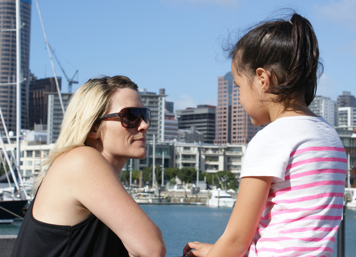A mother and daughter having a conversation in an urban setting
