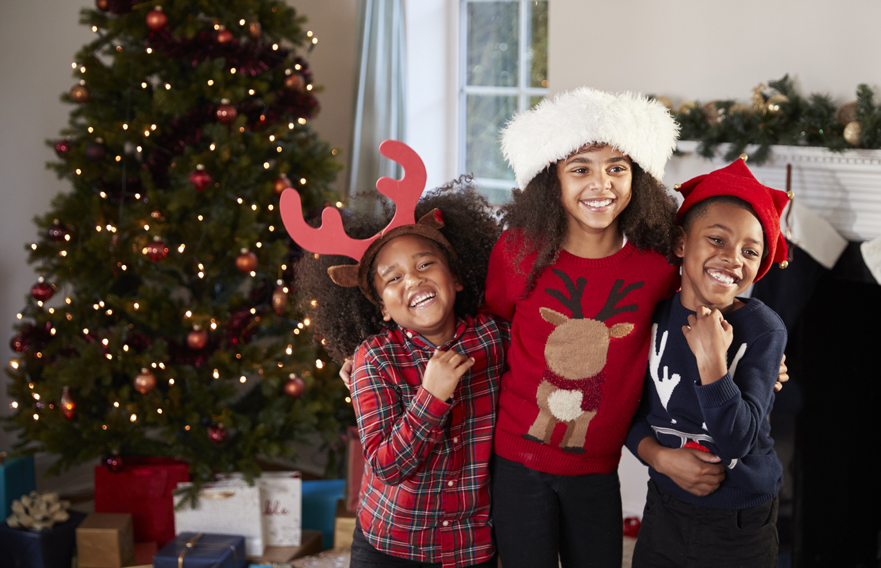 Children Wearing Festive Jumpers And Hats Celebrating Christmas At Home Together