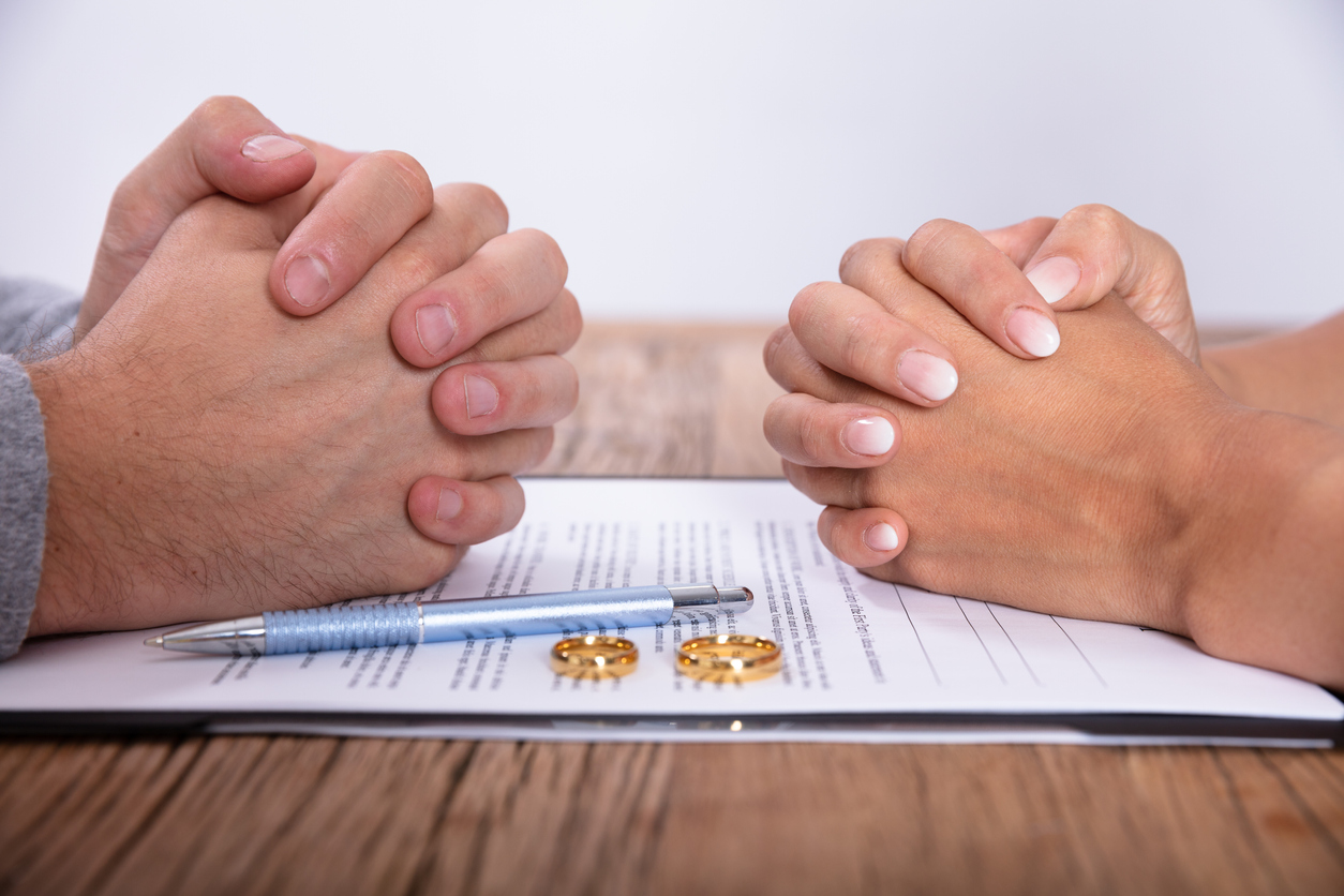Couple's Hand With Divorce Agreement And Golden Wedding Rings On a table