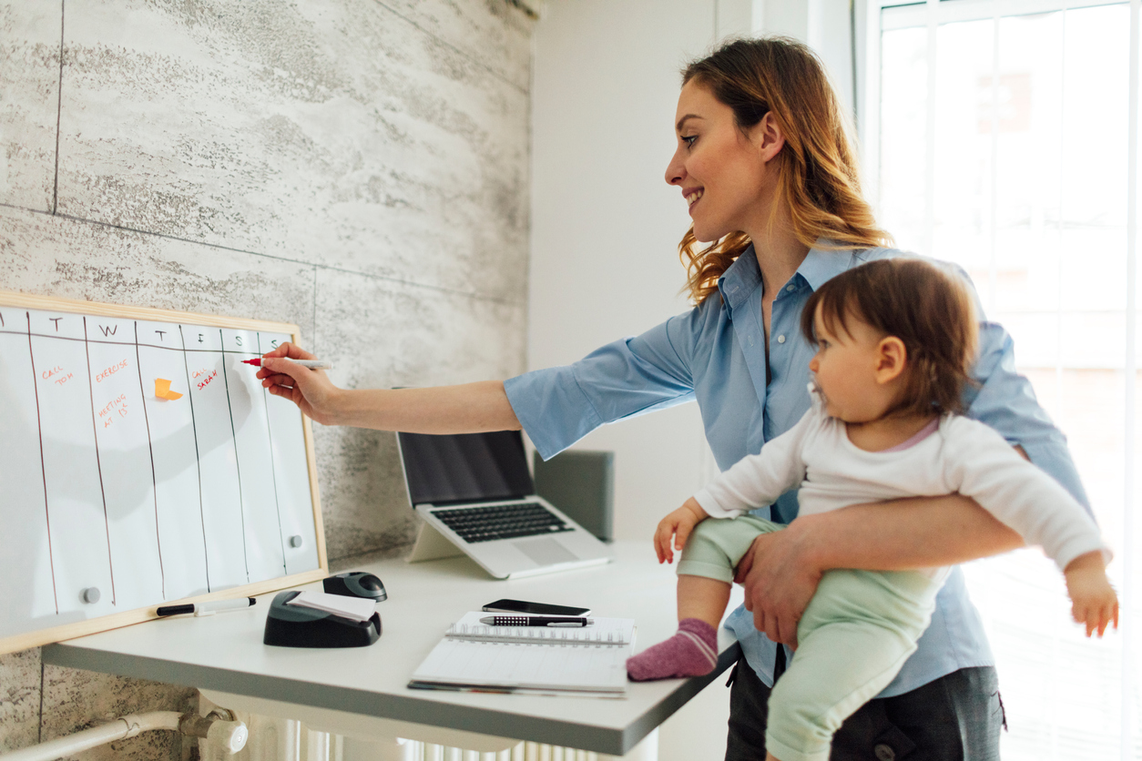 Mother carrying her baby girl while writing on a whiteboard calendar